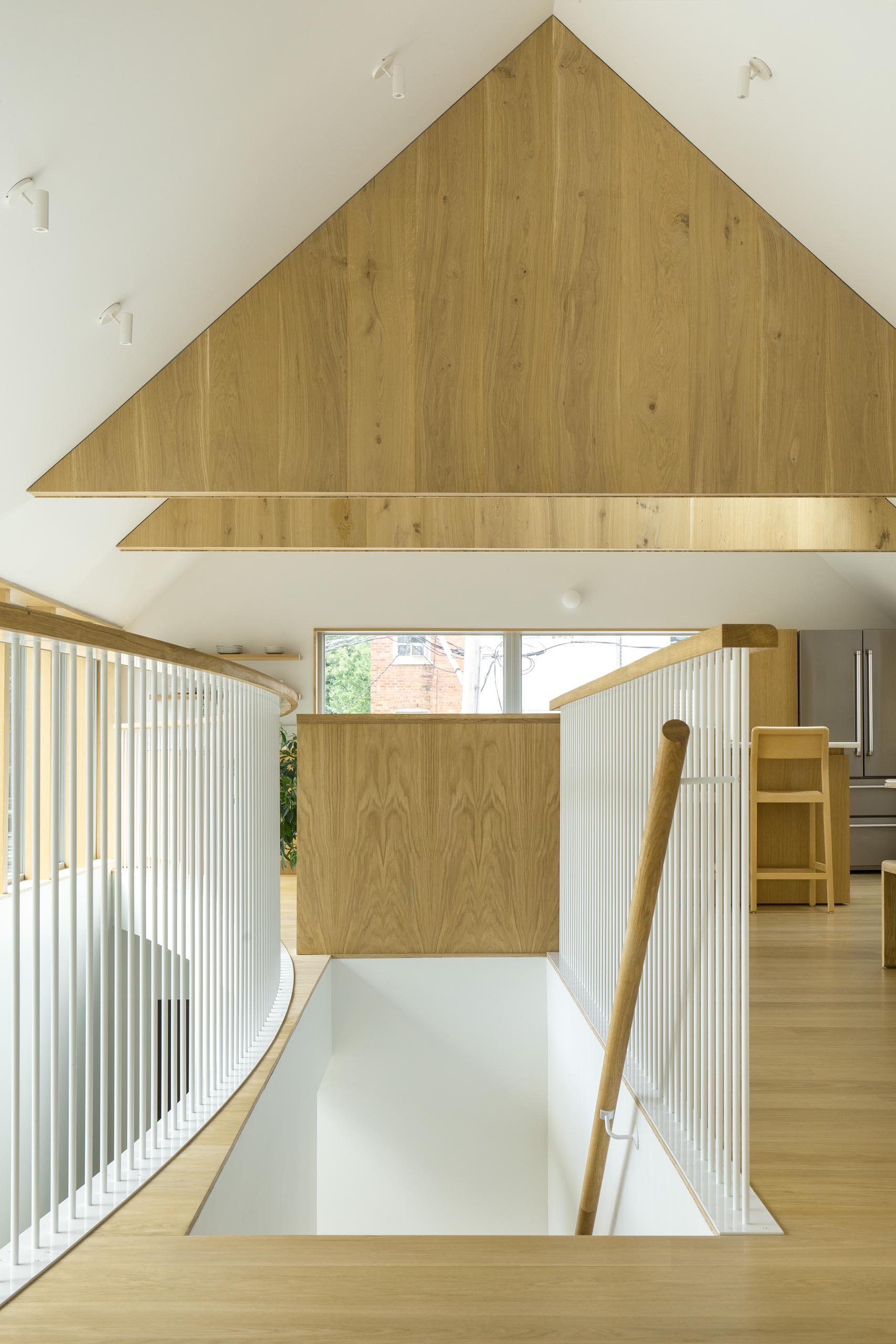 Wood stairs with a matching handrail lead up to the social areas of this modern home.