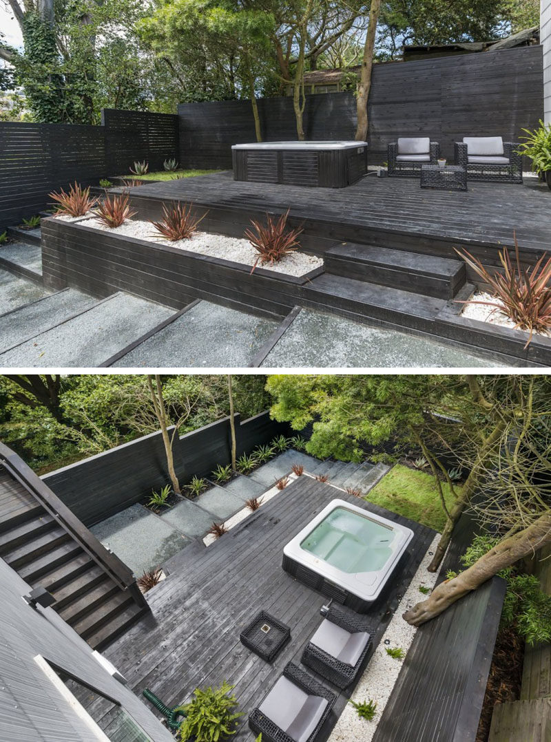 13 Multi-Level Backyards To Get You Inspired For A Summer Backyard Makeover // This backyard has created multiple levels through the use of black wood to make steps, planters, and an elevated deck with an entertaining spot and a hot tub.