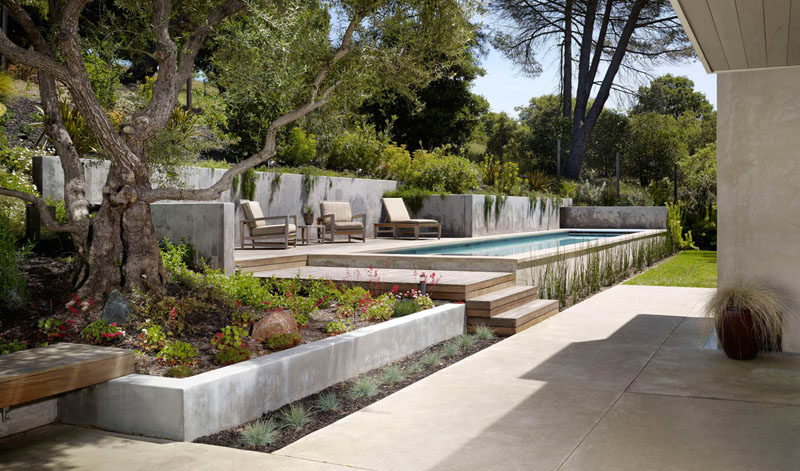 13 Multi-Level Backyards To Get You Inspired For A Summer Backyard Makeover // This backyard is divided into a ground level area with green space and a seating patio, and a second level with a seating area at the same height as the pool.