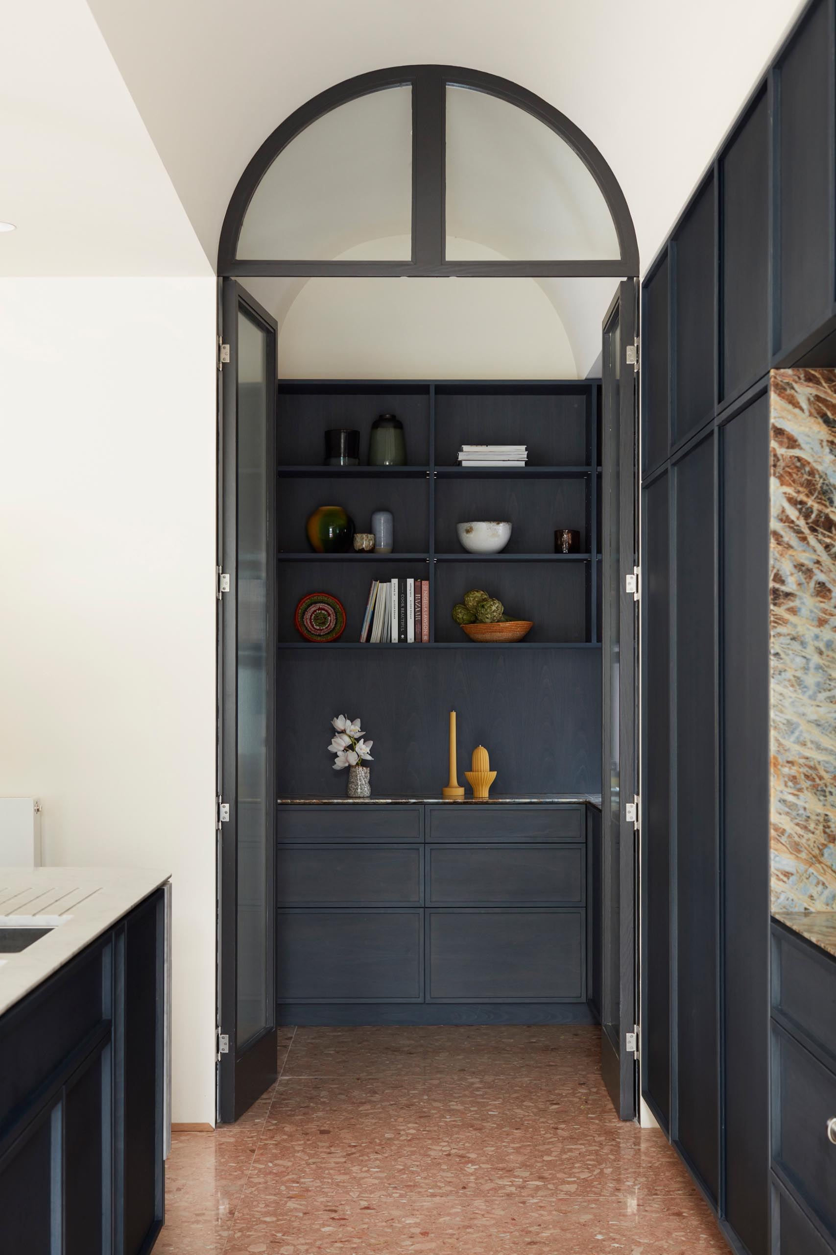 A walk-in pantry with dark cabinets, that's enclosed behind a pair of doors.
