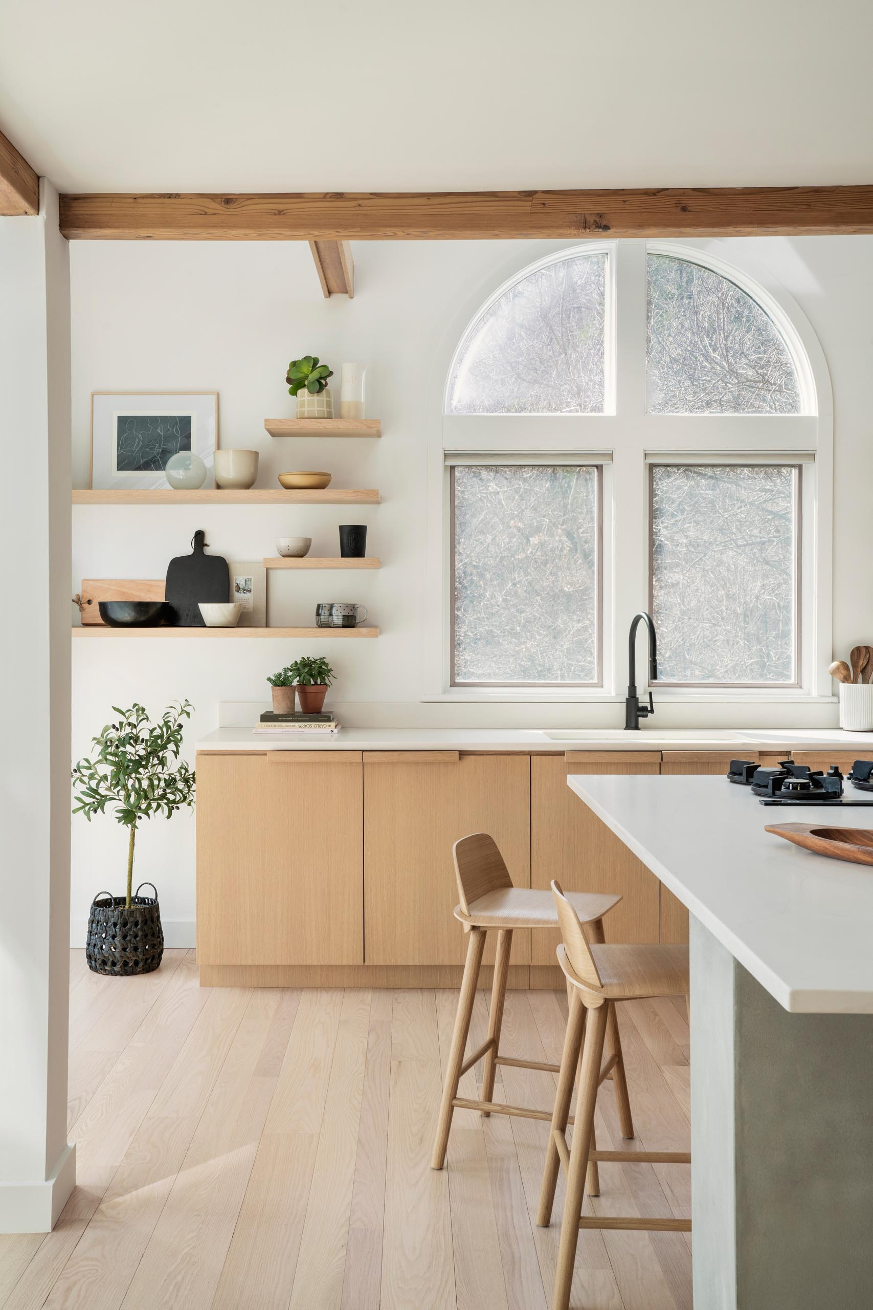 A remodeled kitchen with water-based white rift oak for the cabinets, open shelving, a large island, and quartz countertops.