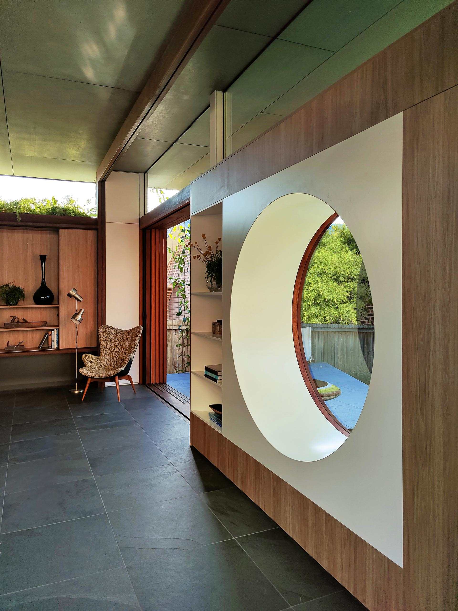 A modern living room with a circular window.