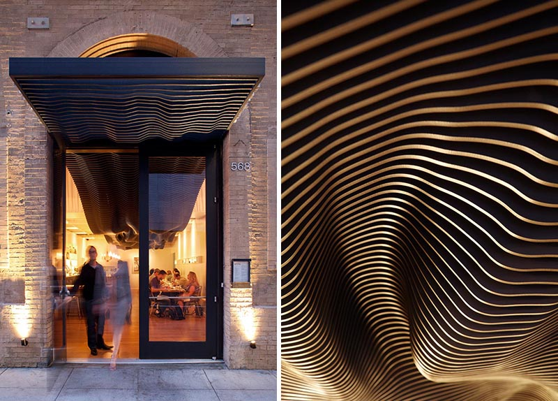 The striking black undulating sculptural detail travels from the interior of the restaurant out to the facade, where it covers the entryway and adds a modern element to the historic building. #BuildingFacade #SculpturalFacade #RestaurantDesign