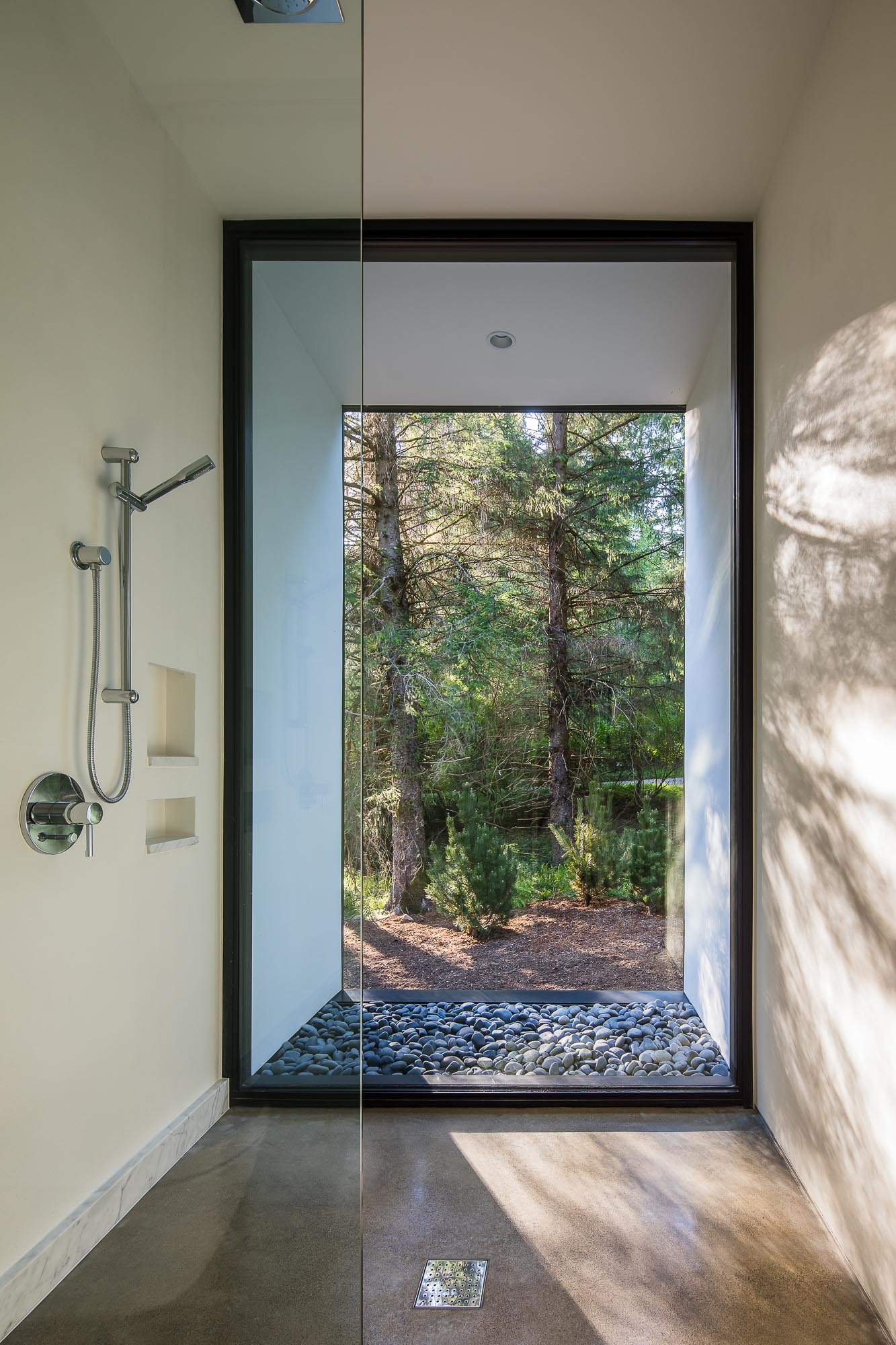 This modern bathroom includes a shower that has an uninterrupted view of the trees.