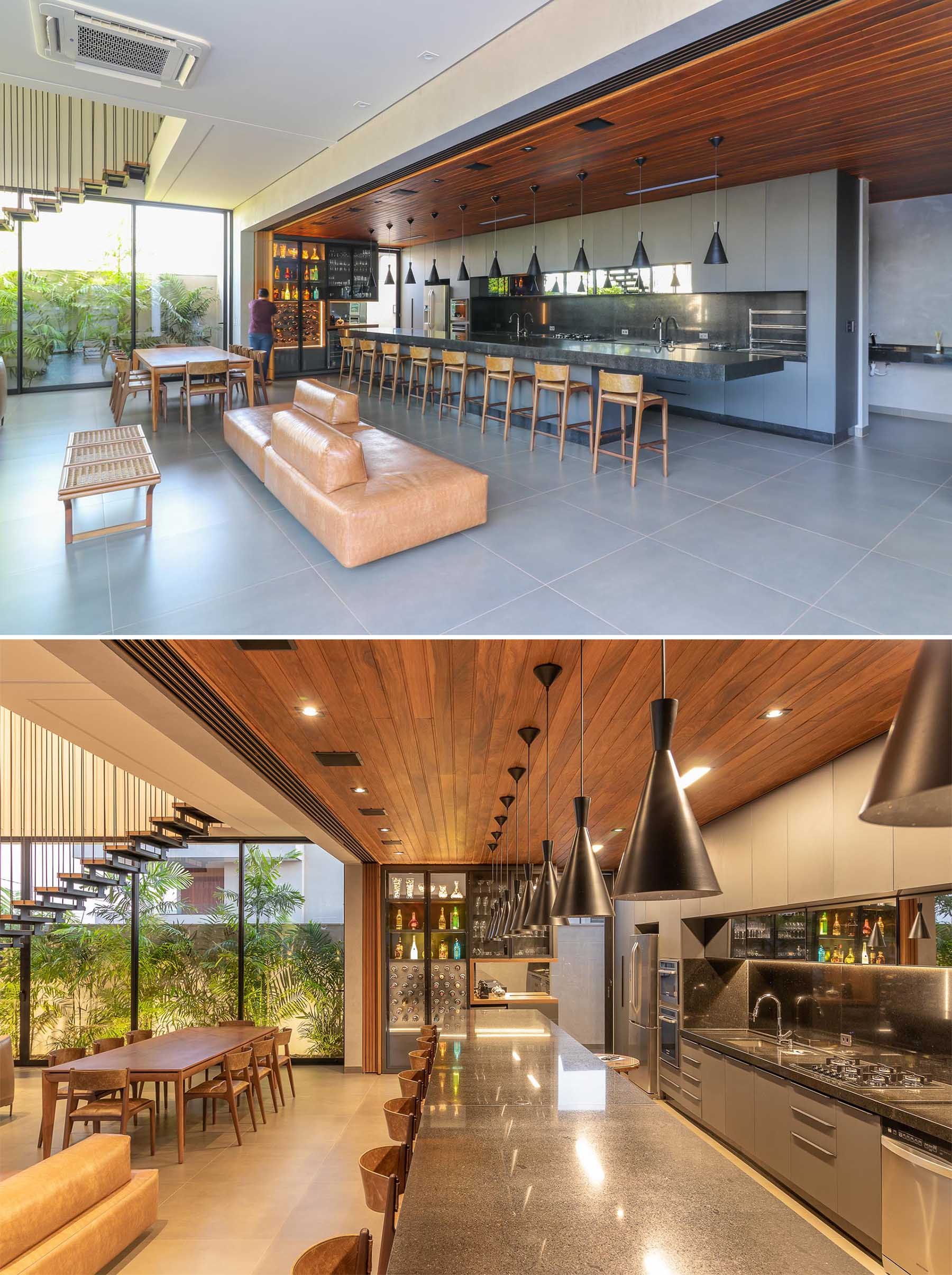 A modern home with a sliding wood wall that can hide the kitchen and expansive island from the open plan dining area and living room.