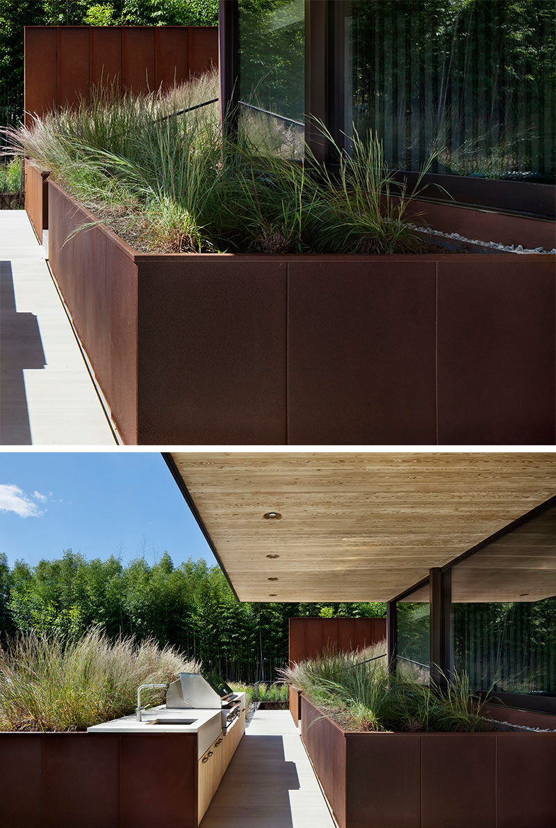 9 Ideas For Including Weathering Steel Planters In Your Garden // Huge planters fill the backyard patio of this family home, and make dinner parties feel like they're taking place in the well-groomed great outdoors. #SteelGardenPlanters #WeatheredSteelPlanters #CortenSteelPlanters #Landscaping #GardenIdeas #PlanterIdeas