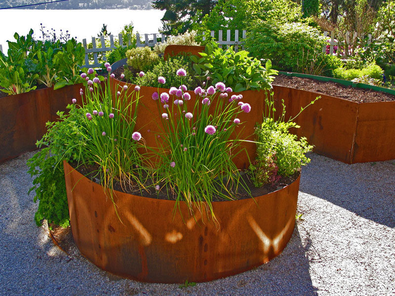 9 Ideas For Including Weathering Steel Planters In Your Garden // This weathered steel planter spirals out of the ground to add height and an artistic touch to the garden. #SteelGardenPlanters #WeatheredSteelPlanters #CortenSteelPlanters #Landscaping #GardenIdeas #PlanterIdeas