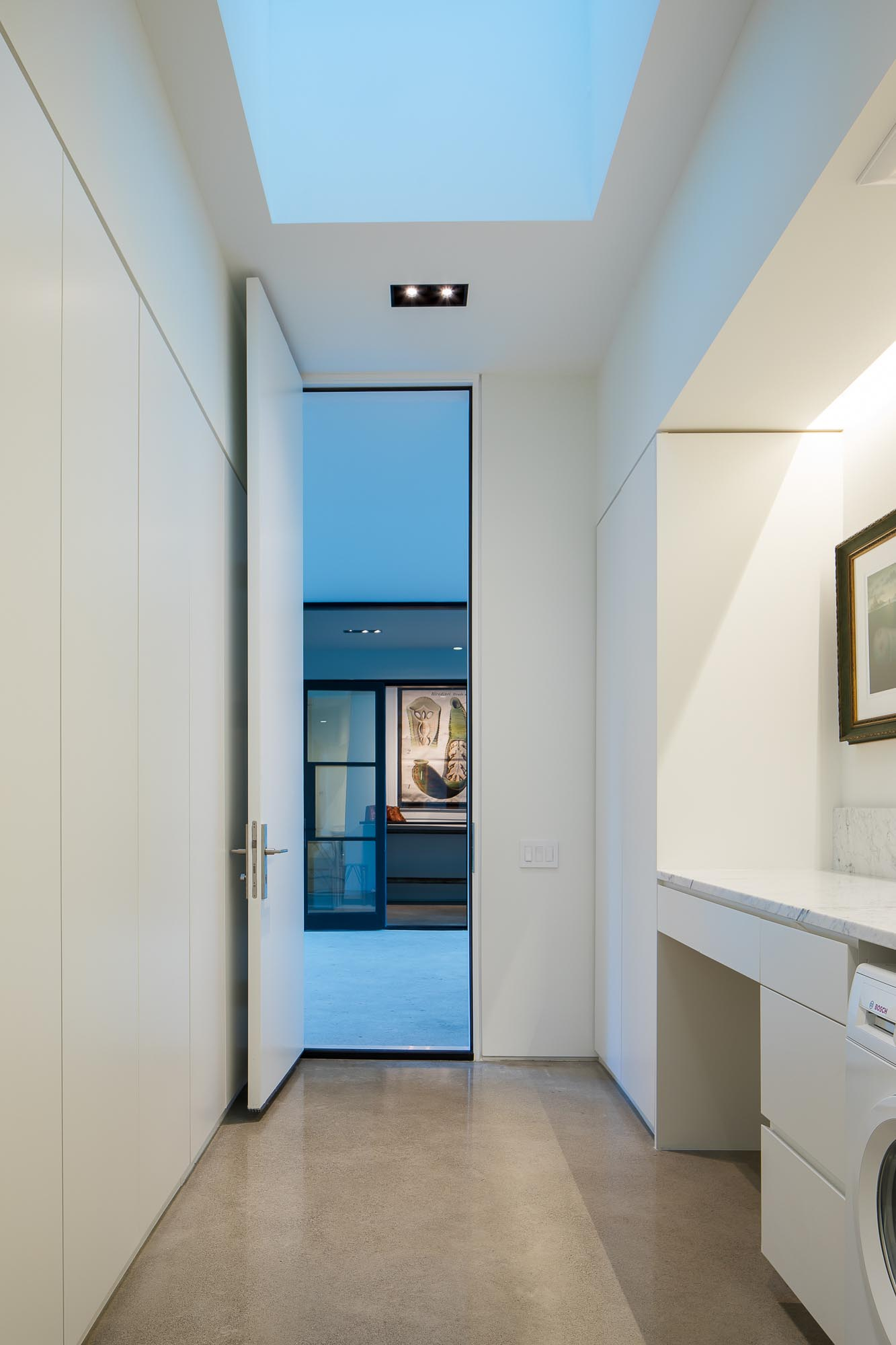 A modern white laundry room with concrete floors.